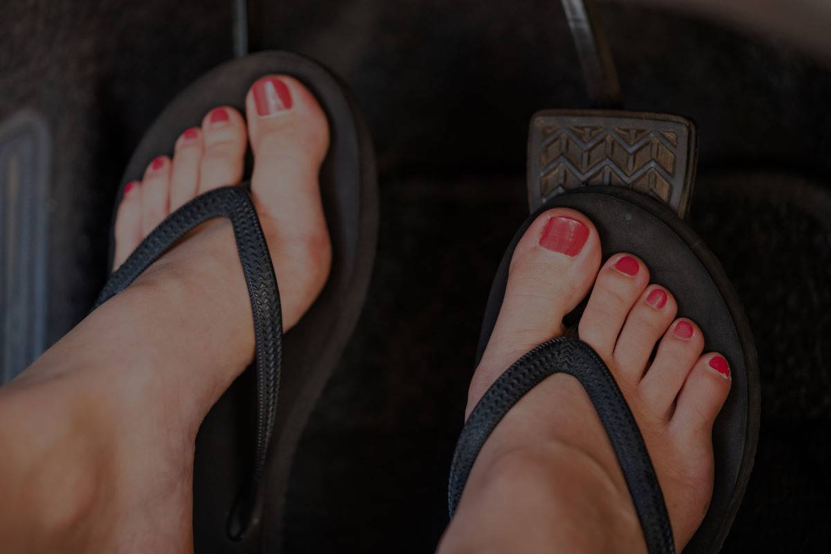 Summer feet driving a car in flip flop shoes
